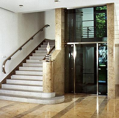 Repräsentativer Treppenaufgang mit Glasaufzug